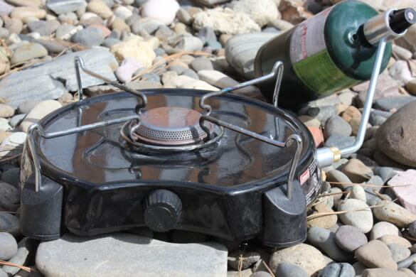 This photo shows the Coleman PowerPack Propane Stove for camping with a propane bottle attached.