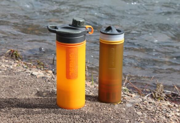 This photo shows the GRAYL GEOPRESS Purifier and GRAYL ULTRALIGHT Purifier on the bank of a creek.