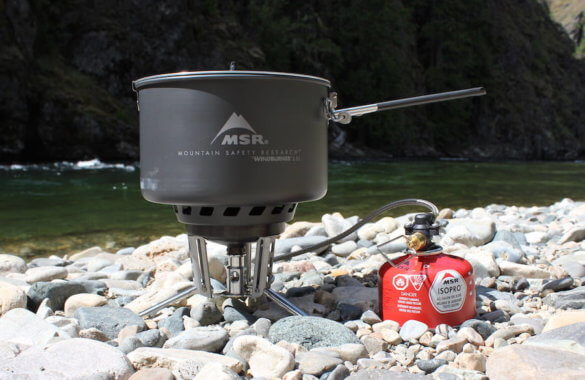 This photo shows the MSR WindBurner Stove System Combo lightweight camping and backpacking stove outside near a river.