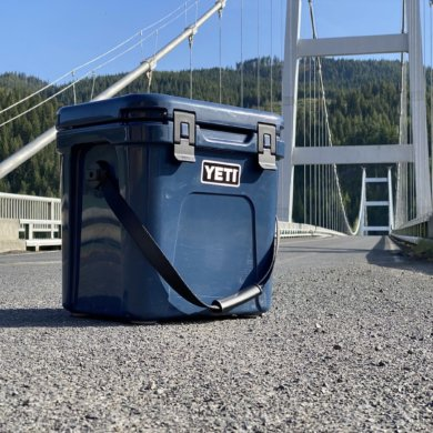 This review photo shows the YETI Roadie 24 cooler on a road near a bridge.