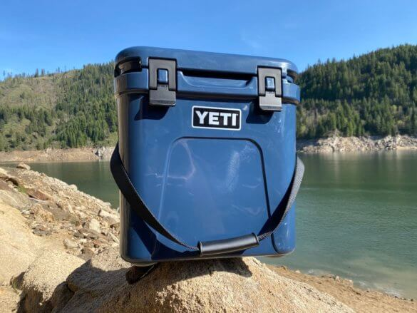 This photo shows the YETI Roadie 24 hard cooler outside near a lake on a day trip.