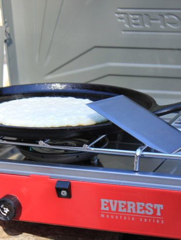 This review photo shows the Camp Chef Everest Two-Burner Camping Stove with a cooking pancake.