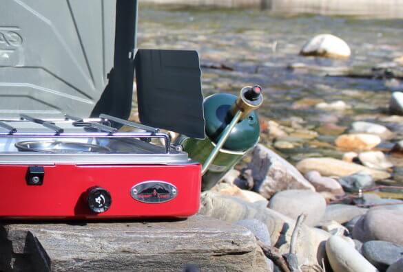 This review photo shows the Camp Chef Everest Two-Burner Camping Stove shows a closeup of the propane bottle attached to the stove.