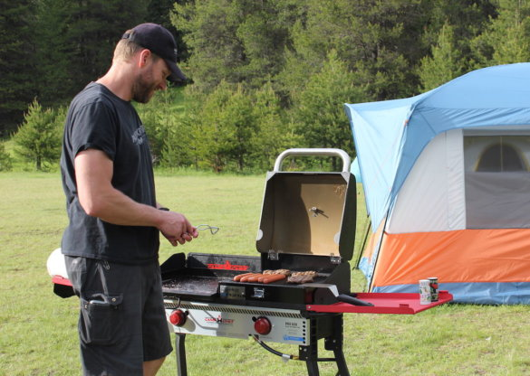 This photo shows the author cooking with the Camp Chef Pro 60X and the BBQ Grill Box and Griddle accessories while out camping and testing gear.