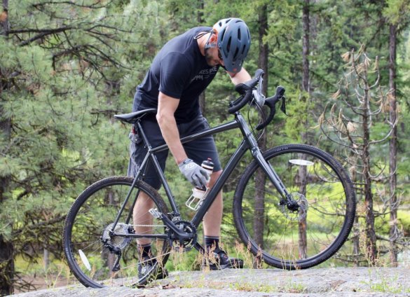 This review photo shows the author taking a break for a drink of water after riding the Cannondale Topstone AL 105 gravel bike during a day of testing.