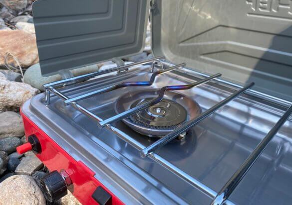 This review photo shows the Camp Chef Everest Two-Burner Camping Stove with one burner lit.