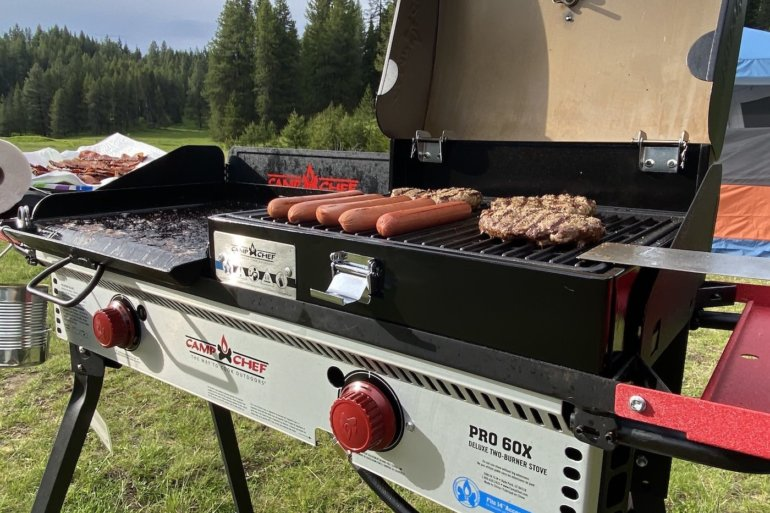 This review photo shows the Camp Chef PRO 60X camping stove being used to cook dinner outside while camping.