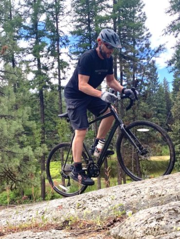 This review photo shows the author testing the Cannondale Topstone AL 105 gravel bike by riding off-road outside.