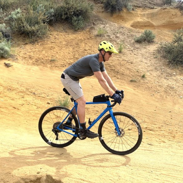 "This testing and review photo shows the author wearing the Showers Pass Gravel 10"" Shorts while riding a gravel bike on a trail during testing."