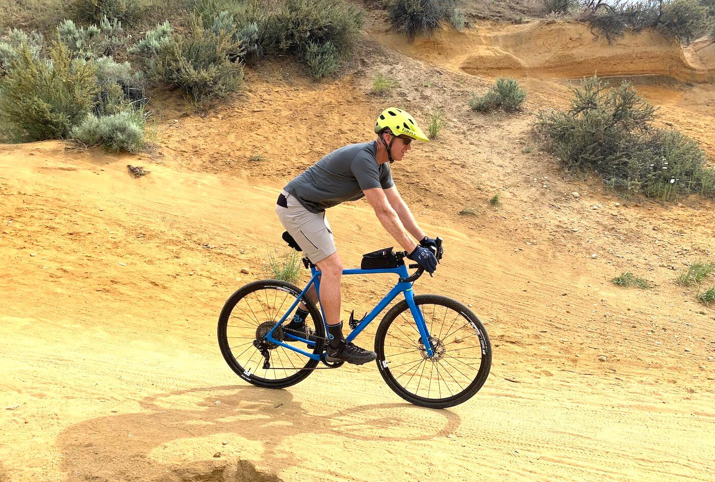 """This testing and review photo shows the author wearing the Showers Pass Gravel 10"""" Shorts while riding a gravel bike on a trail during testing."""