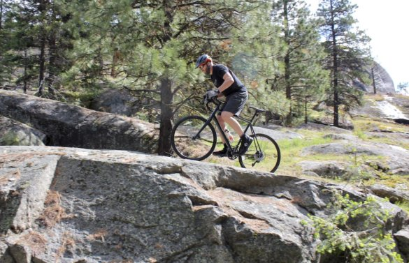 This photo shows the author riding the Cannondale Topstone AL 105 gravel bike off the road an onto a rocky outcropping.