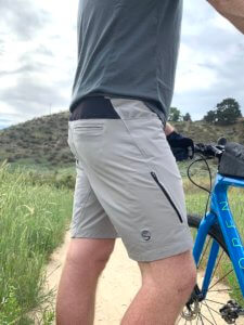 """This photo shows the author wearing the Showers Pass Gravel 10"""" Shorts while standing next to a gravel bike during testing."""