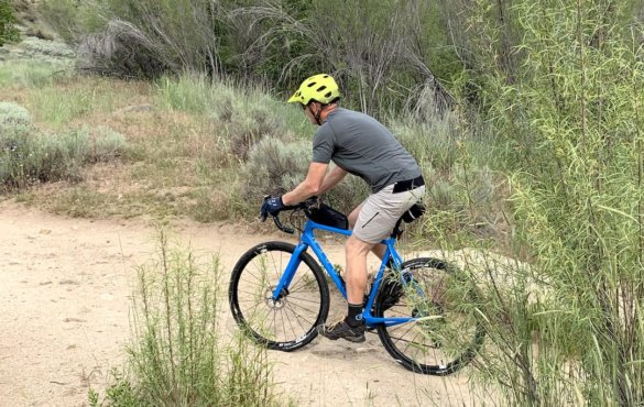 """This review photo shows the author testing the Showers Pass Gravel 10"""" Shorts for men by riding a gravel bike on trails."""