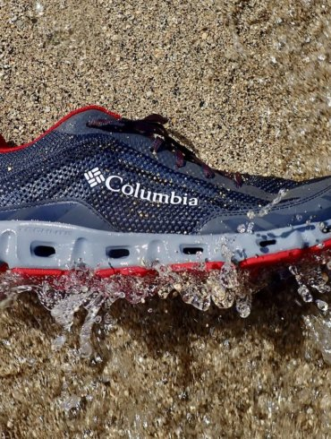 This testing and review water shoe photo shows a closeup of a Columbia Drainmaker IV water shoe on a beach getting hit by a wave.