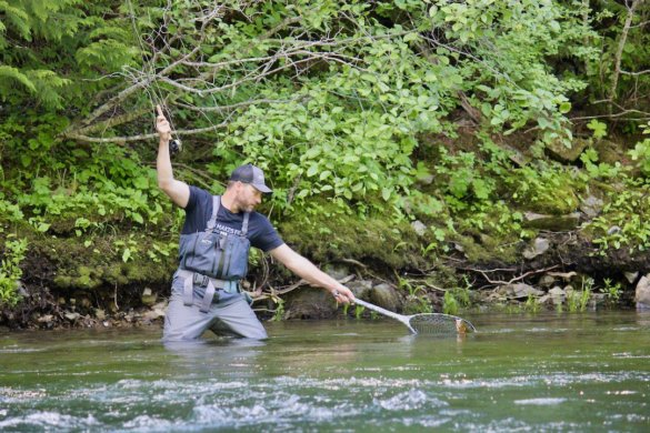 This photo shows the author caching a trout while wearing the Patagonia Swiftcurrent Expedition Zip-Front Waders.
