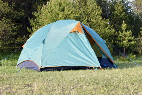 This photo shows the Kelty Wireless 4 Tent setup at a camping spot with the rainfly on.