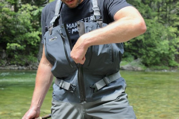 This photo shows a fly fisher using the zipper on the Patagonia Swiftcurrent Expedition Zip-Front Waders.