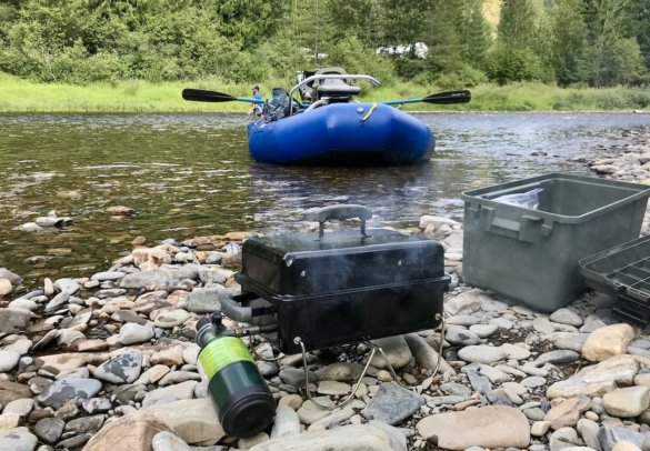 This review photo shows a portable grill on a riverbank with the NRS STAR Outlaw 140 Raft in the background.