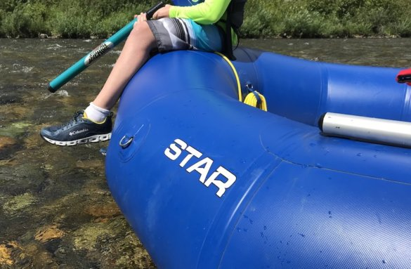 This photo shows a swimmer sitting on the front of the STAR Outlaw 140 Raft while floating on a river.