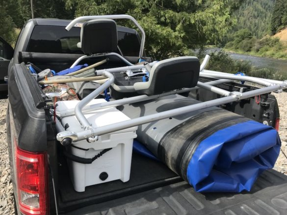 This photo shows a STAR Outlaw Raft and an NRS fishing frame system all packed up in the bed of a pickup truck.