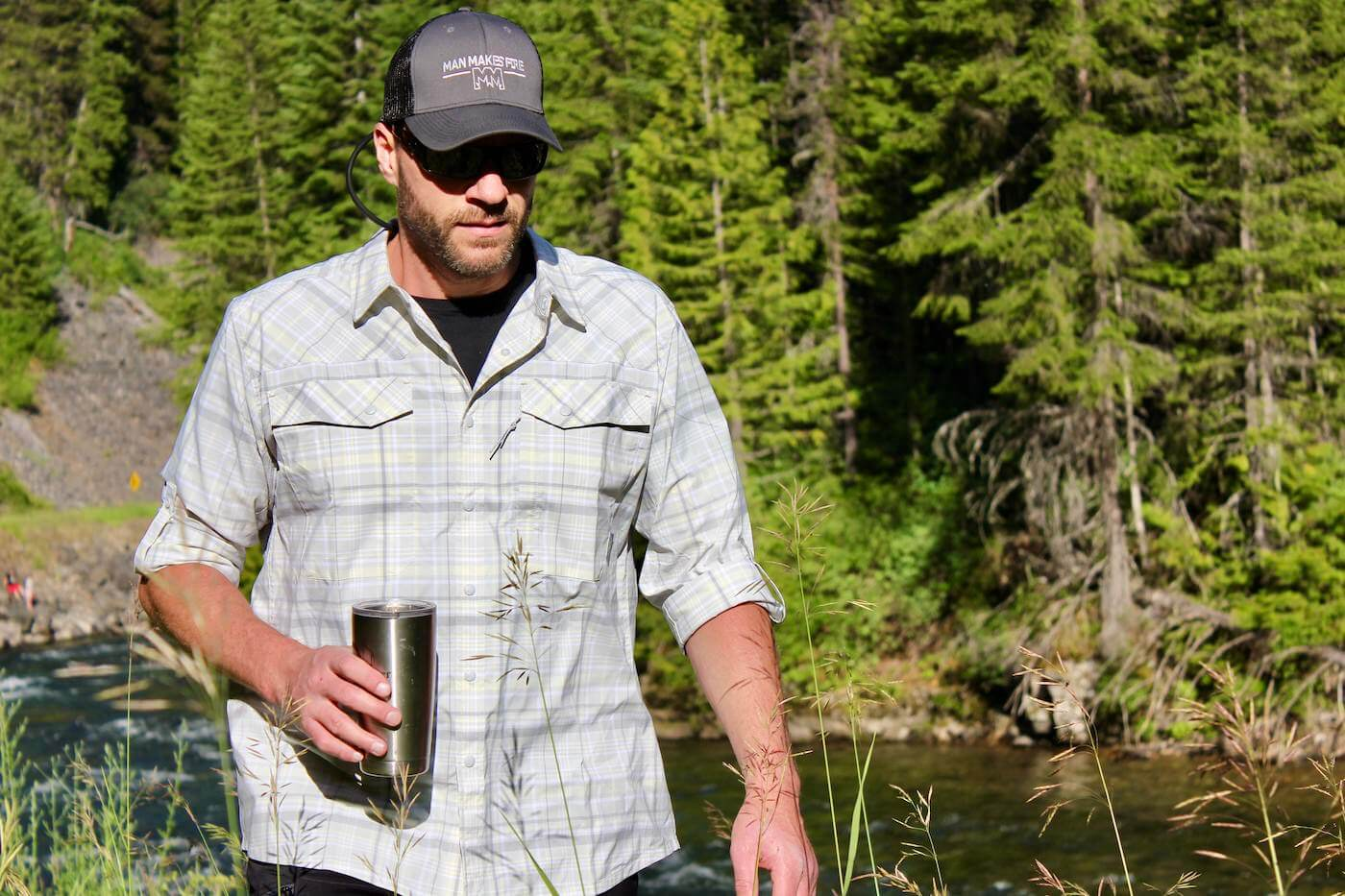 This photo shows the author wearing, testing, and reviewing the Stio Eddy Drift LS shirt near a river.