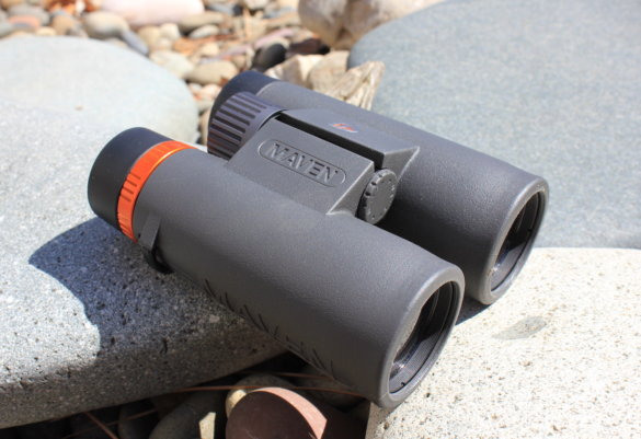 This review and testing photo shows the Maven C.1 10x42 Binoculars outside on a rock.