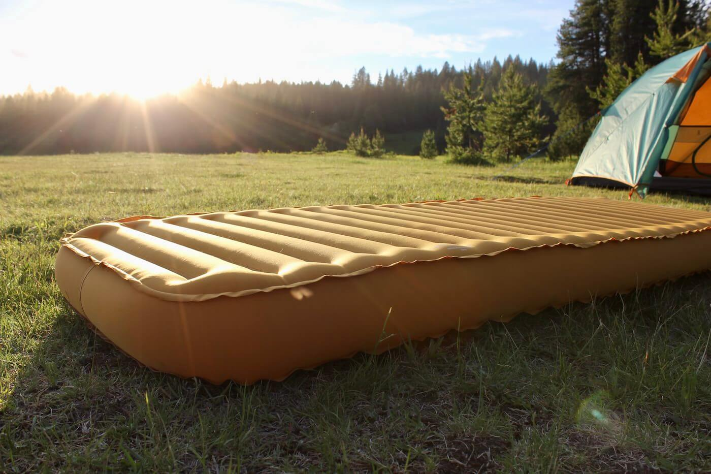 This photo shows the REI Camp Dreamer Insulated Air Sleeping Pad inflated outside at a camping spot.
