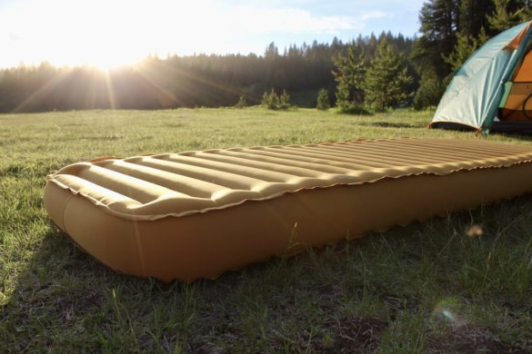 This photo shows the REI Co-op Camp Dreamer Insulated Air Sleeping Pad at a campsite near a camping tent.