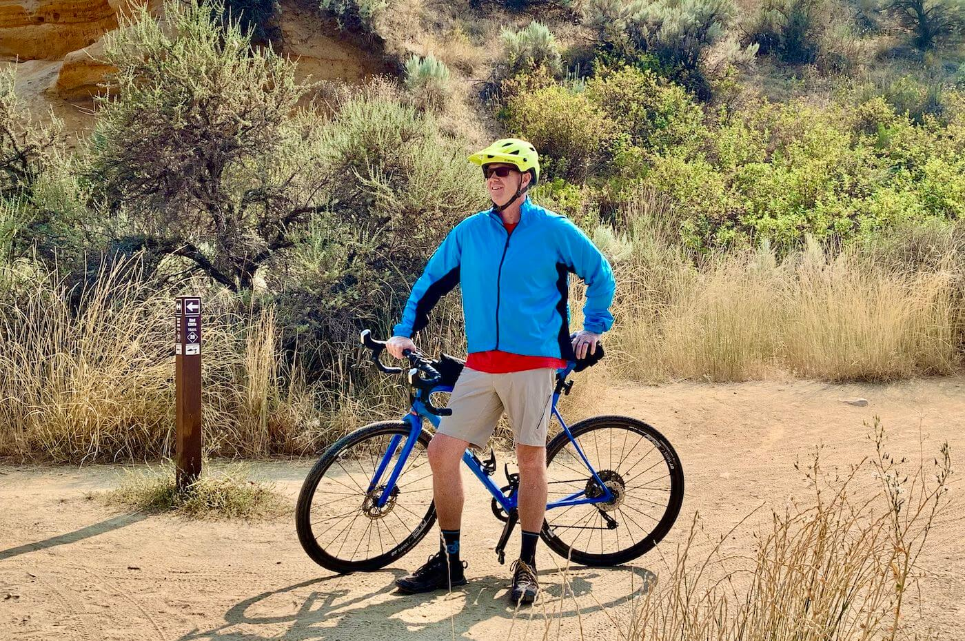 This review and testing photo shows the author wearing the Showers Pass Ultralight Wind Jacket on a trail with a gravel bike.