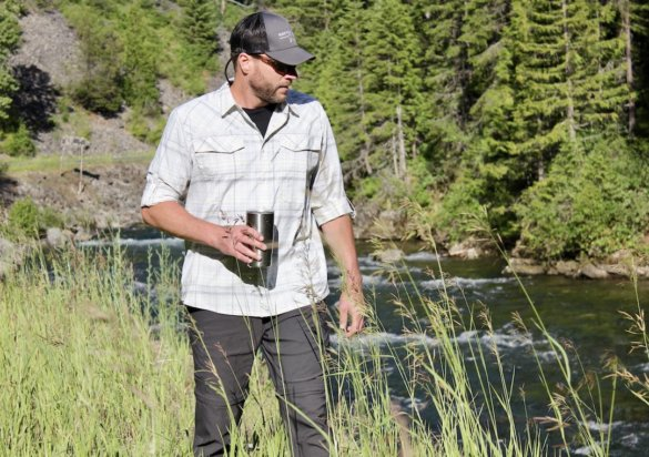 This photo shows the author wearing the Stio Coburn XT Convertible Pants while testing and reviewing near a river.