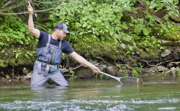 This photo shows the author fly fishing on a river using the Fishpond Nomad Mid-Length Net to net a trout.