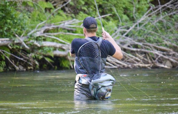 This photo shows the author fly fishing in a river with the Fishpond Nomad Mid-Length Net tucked behind a fly fishing waist pack.