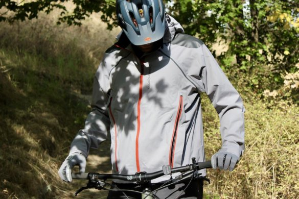This photo shows the author testing the Showers Pass Elements Jacket on a mountain bike.