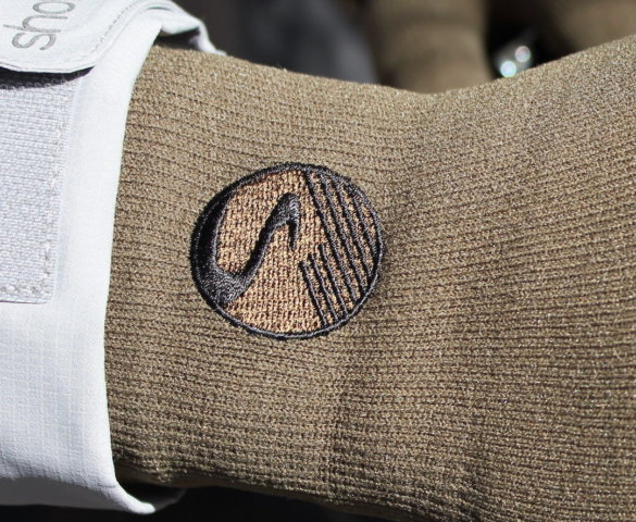 This photo shows a closeup of the Showers Pass stitched logo on the Crosspoint Waterproof Knit Wool Gloves.