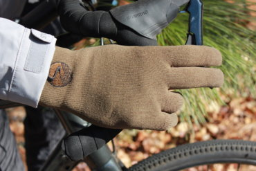This review photo shows the Showers Pass Crosspoint Waterproof Knit Wool Gloves being worn on a gravel bike by the author.