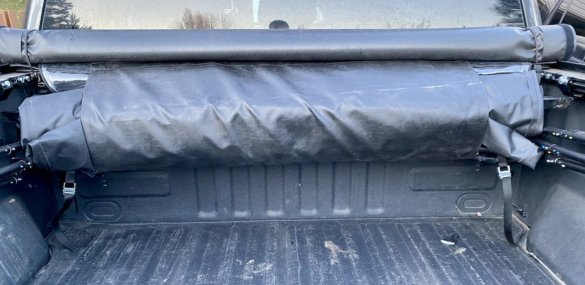 This photo shows the Fas-Top topper folded up for storage along the bed of a pickup.