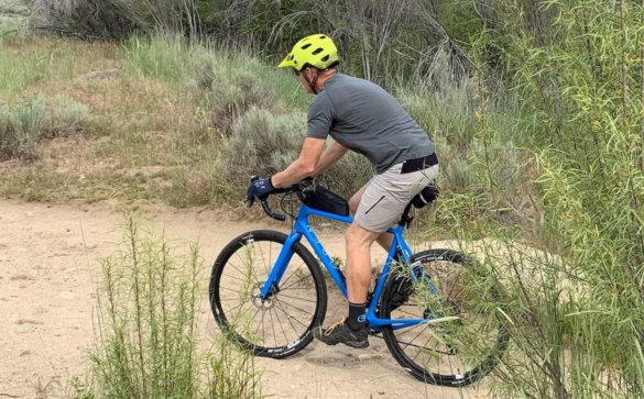 This review photo shows the author wearing the men's Apex Merino Tech Shirt while riding a gravel bike on trails.