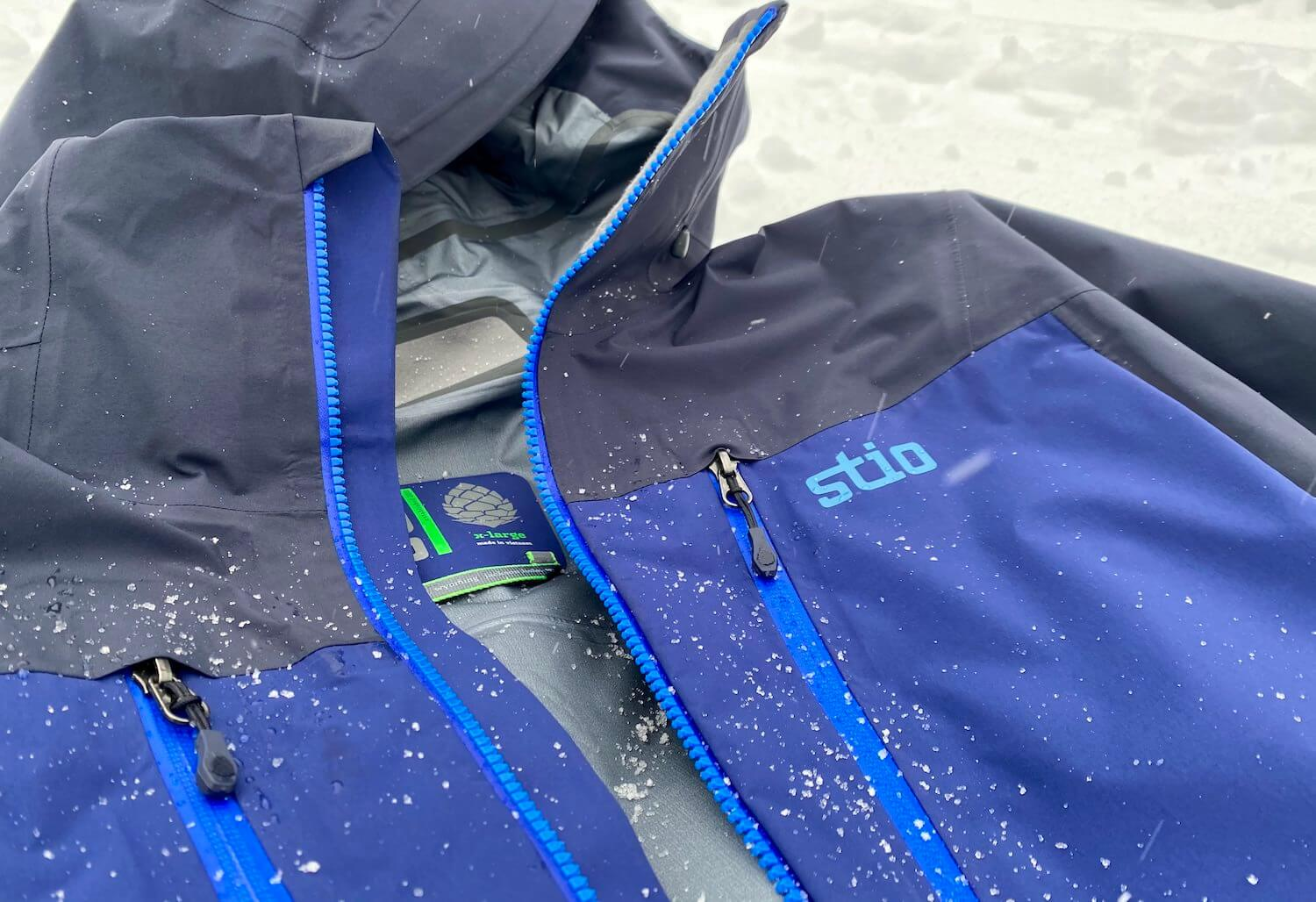 This review photo shows the Stio Objective Pro Jacket outside in a closeup with snow during the testing process.