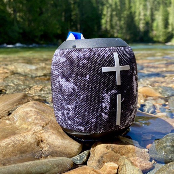 This review photo shows the Ultimate Ears Wonderboom 2 waterproof bluetooth speaker outside near a river.