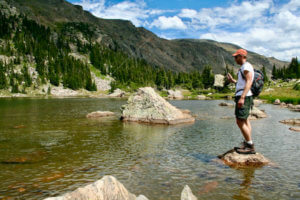 This fly fishing rod and reel combo photo shows a fly fisher fishing on a mountain lake with a fly rod and reel combo.