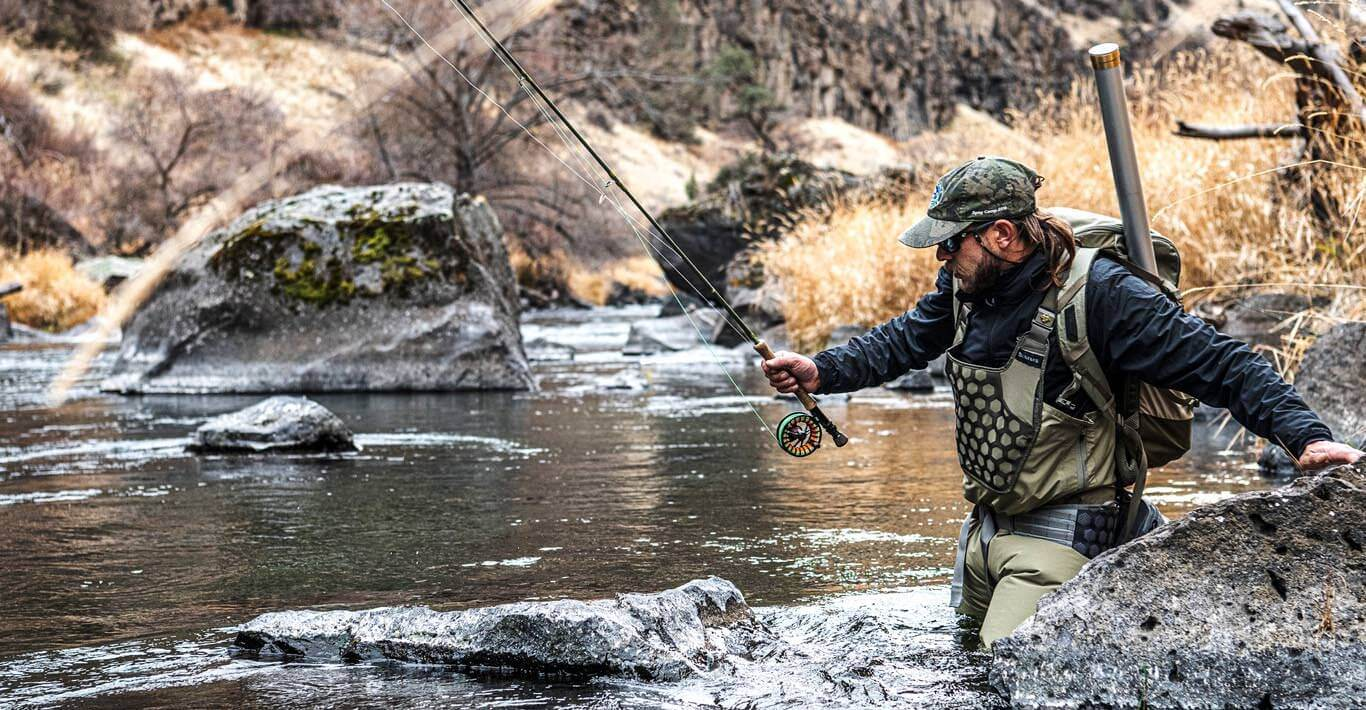 This photo shows a fly fisherman wading in a river while wearing the Simms Flyweight Waders.
