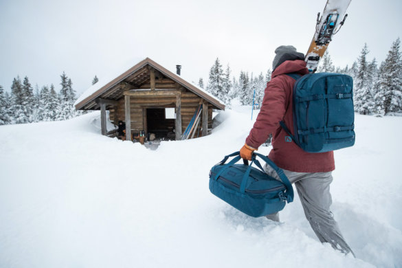 This photo shows a skier carrying a YETI Crossroads Collection duffel bag and backpack.