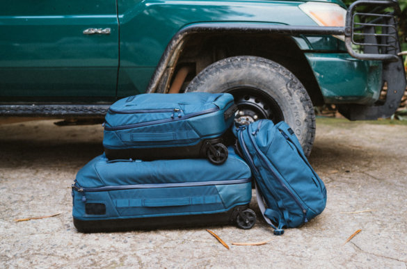 This photo shows YETI Crossroads Collection backpacks and luggage outside near a vehicle.