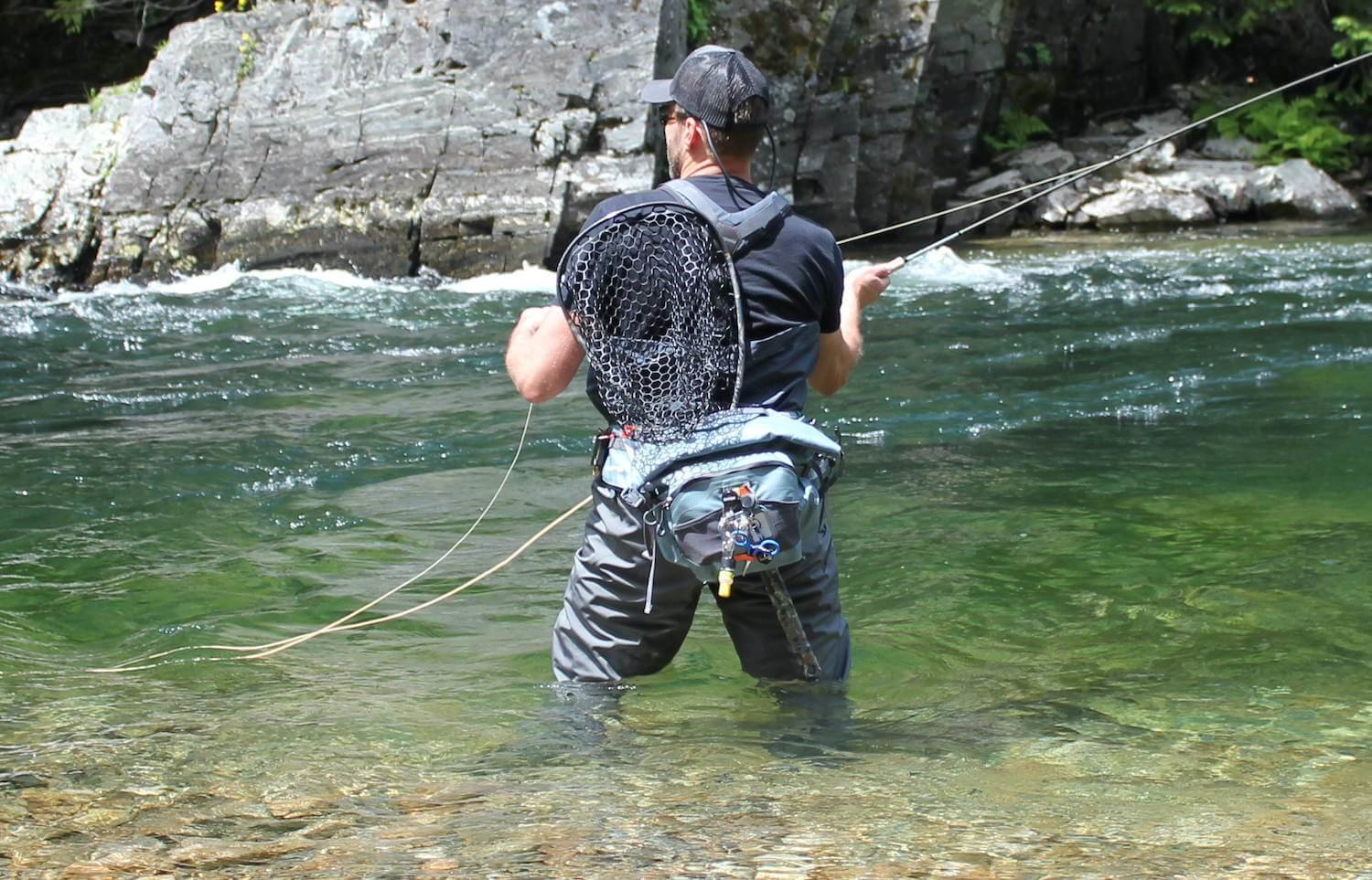 This best fly fishing hip pack photo shows the author testing a fishing hip pack in a river while fly fishing during the review process.
