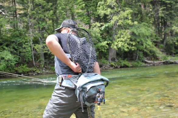 This photo shows the author demonstrating how to carry and access a fly fishing net with a fly fishing hip pack.