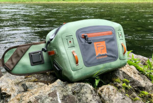 This photo shows the Fishpond Thunderhead Submersible Lumbar Pack near a river.