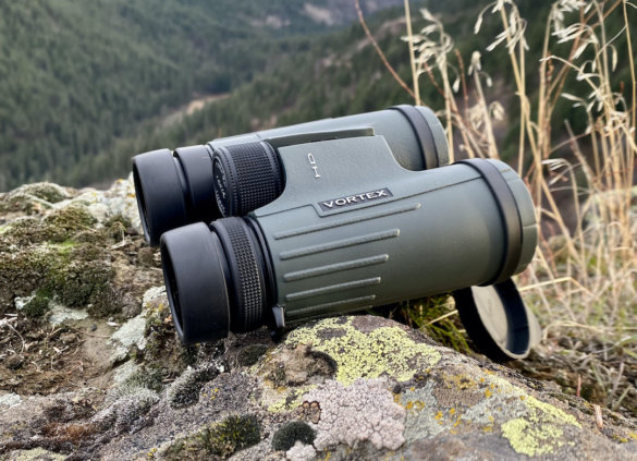 This hunting gear review image shows the Vortex Viper HD 10x32 binoculars outside on a rock near a cliff in a forest.