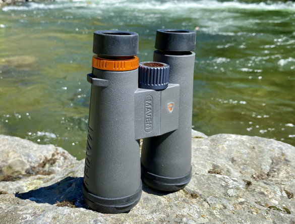 This review photo shows the Maven C.3 10x50 binoculars standing upright on a rock outside near a river.