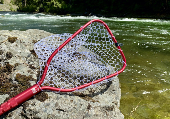 This review photo shows the Rising Brookie Net in the red option with a river in the background.