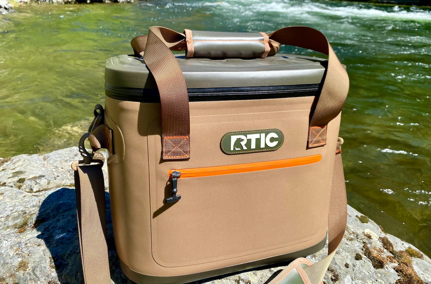 This review photo shows the RTIC Soft Pack 30 Cooler next to a river.
